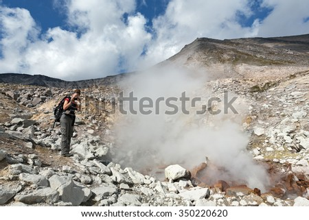 DZENZUR VOLCANO, KAMCHATKA PENINSULA, RUSSIA - SEP 04, 2014: Beautiful girl photographing the smoking (steaming) fumarole on crater active Dzenzur Volcano on a sunny day. Russia, Far East, Kamchatka. - stock photo