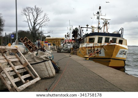 Dziwnow, Poland November 14, 2015: Cutters and fishermen after fishing during dark, stormy day. They unload fish and repair nets. Polish fishing industry. - stock photo
