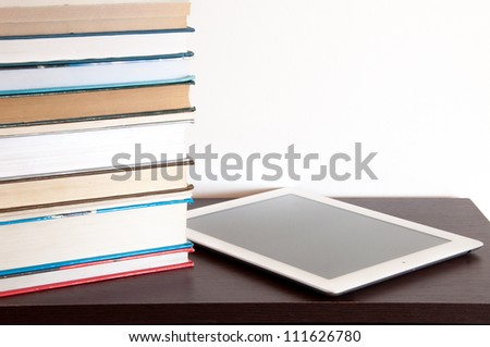 E-book reader and stack of books on a table - stock photo
