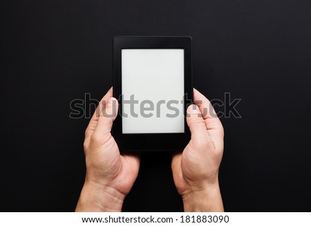 E-book reader or tablet pc in hand. Black background - stock photo
