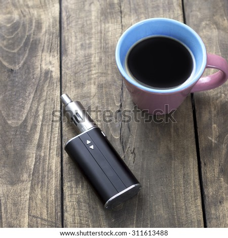 e-cigarette and cup of coffee on table, from above - stock photo