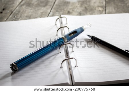 E-cigarette on notepad on wooden table - stock photo