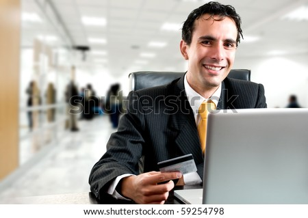 e-commerce concept: business man paying online with his credit card at office - stock photo