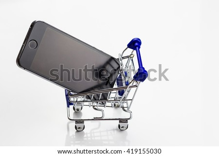 E-commerce Concept. Shopping Cart with cellphone on a white background. - stock photo