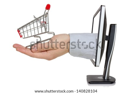 E-commerce conception. Computer monitor and hand with shopping cart - stock photo