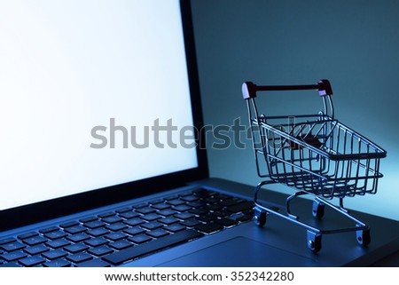 E-commerce. Miniature shopping cart on laptop computer. - stock photo