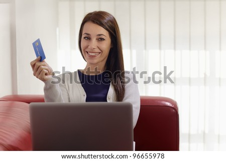 E-commerce with happy woman using pc and credit card while shopping on the web at home - stock photo