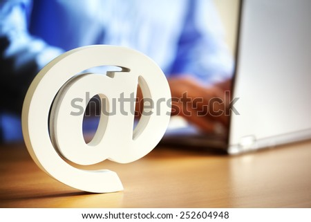 E-mail at symbol on an office desk with man on laptop computer - stock photo