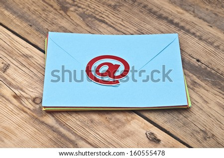 E-mail symbol and pile colorful envelopes on old wooden background - stock photo