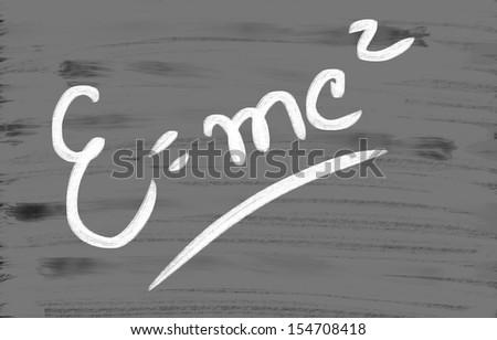 E=mc2 handwritten with chalk on a blackboard - stock photo