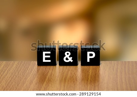E&P or Exploration and Production (upstream oil and gas industry) on black block with blurred background - stock photo