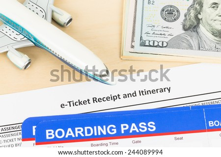 E-ticket with plane model, banknote, and boarding pass - stock photo