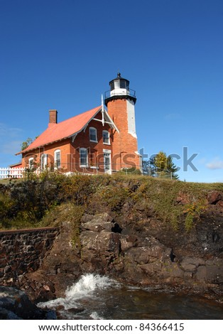 Eagle Harbor Lighthouse sits proudly on a cliff overlooking Lake Superior on the Keweenaw Peninsula, Michigan.  A brick structure with lighthouse keeper dwelling attached. - stock photo