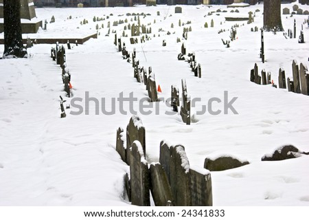 early american gravestones and cemetery  covered in snow during storm