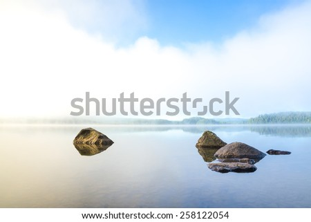 Early and harmonious morning with fog over the lake in northern Sweden - stock photo