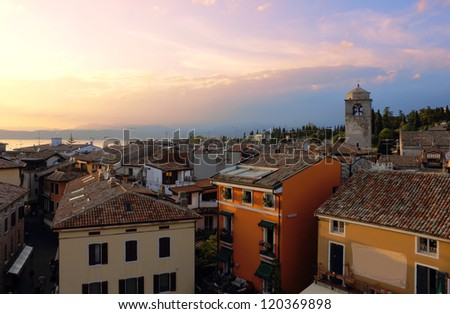 Early evening view of Sirmione in the warm light of the sunset with Lago di Garda at the background. - stock photo