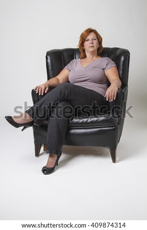 early forty woman with red hair sitting in a black leather love seat - stock photo