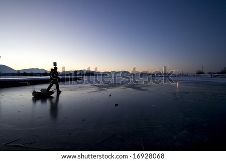 Early in the Morning a Fisherman Walking on Ice to Catch Fish