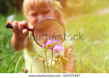 Early learning - little girl examining batterfies with magnifying glass