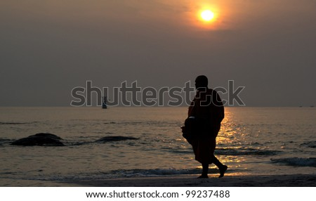 Early morning activity of monk on the beach at Huahin Thailand.
