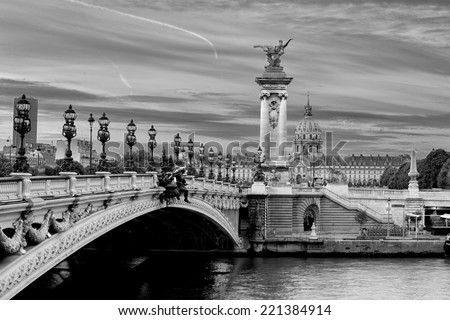 Early morning, black and white, view on the famous landmark Alexander iii bridge in Paris, capital of France, with beautiful clouds in the sky and the golden statue catching the first sunrays - stock photo