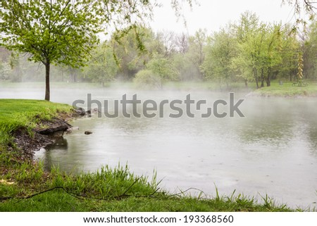 early morning fog lingering over the lake with vivid green trees surrounding it - stock photo