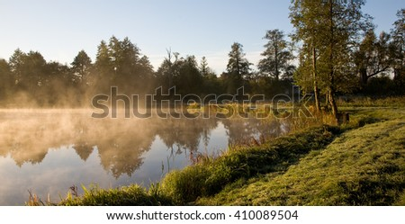 Early morning fog over calm water of pond,Bialowieza,Palace park,Poland,Europe - stock photo