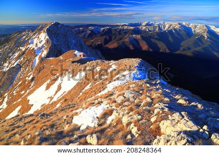 Early morning light on the mountains and distant red refuge  - stock photo