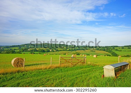 Early morning light over a field of hay bails with views over the Cotswold Countryside, Painswick, Gloucestershire, United Kingdom - stock photo