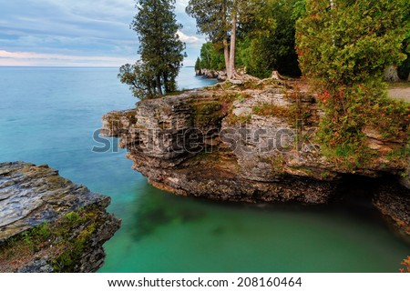 Early morning long exposure photo at Door County, Wisconsin's Cave Point, on Lake Michigan, reveals rocky cliffs, colorful waters, and a cloudy sky. - stock photo