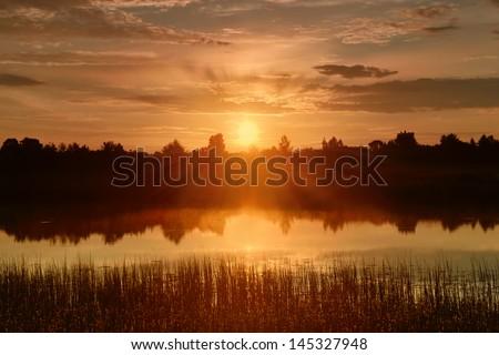 Early morning on the lake. Beautiful sunrise. - stock photo