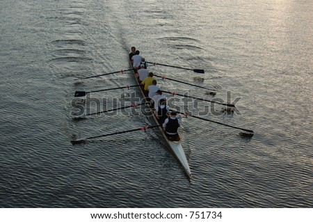 Early morning rowers training on the river. - stock photo