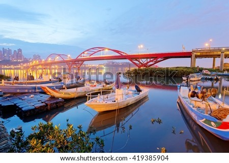 Early morning scenery of boats parking by riverside and in the background, the beautiful landmark Guandu Bridge spanning across Tamsui River in Taipei, Taiwan, Asia - stock photo