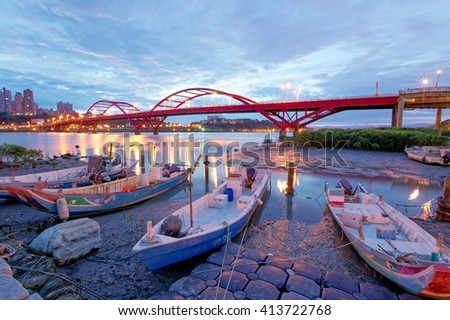 Early morning scenery of stranded boats by riverside during low tide and in the background, the beautiful landmark Guandu Bridge spanning across Tamsui River in Taipei, Taiwan, Asia - stock photo