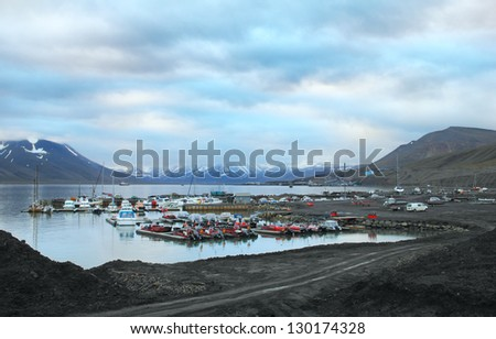 Early morning scenic view - marine terminal against the background of mountain range and dramatic blue sky in port of Longyearbyen, Advent Bay, Spitsbergen (Svalbard island), Norway, Greenland Sea - stock photo