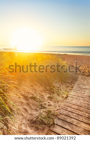 Early morning sun floods the sand dunes and sign on a Manie beach - stock photo