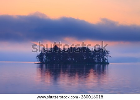 Early morning sunrice at the forest lake with small island, red colors in the sky  - stock photo