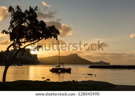 Early morning sunrise at dawn illuminates clouds over Diamond Head and Waikiki Beach area of Oahu in Hawaii - stock photo