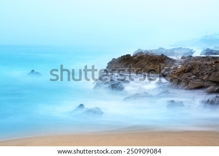 Early morning sunrise cases beautiful light onto a reef where slow shutter speeds capture the motion of the breaking waves. - stock photo