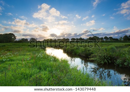 Early morning sunrise over small river on a summer day