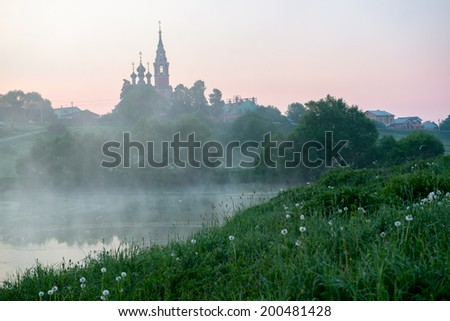 Early morning sunrise village in Russia. Landscape with a church at the hill top - stock photo