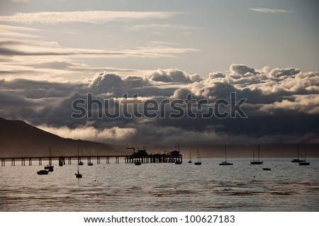 Early morning view of a pier and the coastal mountains of central California on the San Luis Obispo Bay.