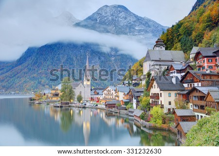 Early morning view of Hallstatt with reflections on smooth lake water, a lakeside village in Salzkammergut region of Austria, in the colorful autumn season