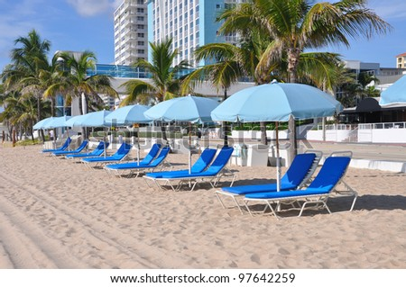 Early Morning View of Lounge Chairs Umbrellas on sandy beach in Fort Lauderdale Florida - stock photo