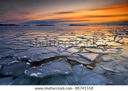 Early morning winter landscape with sunrise and ice floats, in the sea coast of Helsinki, Finland - stock photo