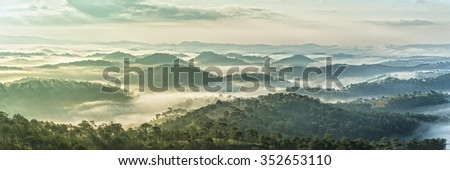 Early on a sunny plateau sunny with warm colors,  below clouds covered hills cradling durable as on planes Elysium. The vast pine forests between clouds crept created many impressive sight - stock photo