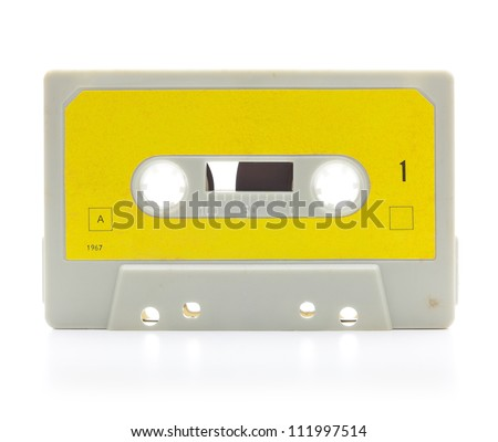 Early 70's cassette tape isolated on white with slight reflection.  Yellow label. - stock photo