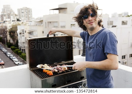 Early 30's caucasian man giving the camera a joyful smile while standing on the roof of a building in urban surroundings, grilling some meat and vegetables. - stock photo
