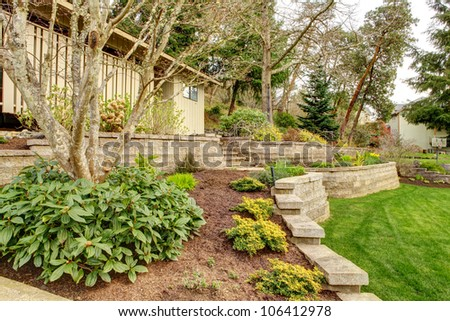 Early Spring Landscape with retaining walls and garage on the back. - stock photo