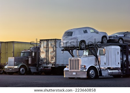 Early sunrise happens over a group of trucks parked at a truck stop. - stock photo
